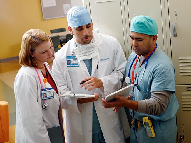 Kaiser Permanente physicians and surgeons consulting with each other while looking at a tablet computer.