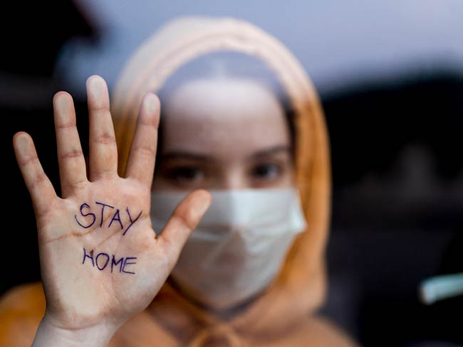 Teenage girl with a surgical maks standing and looking through the window and showing 'stay home' message written on her hand
