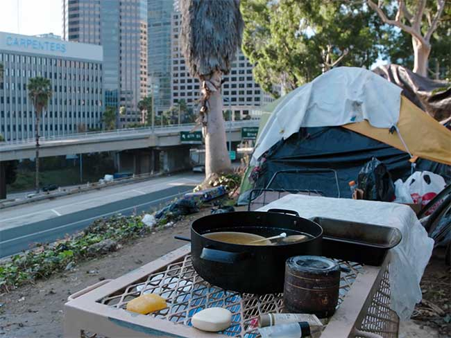 A tent, with a pot of soup in front, next to a freeway overpass.