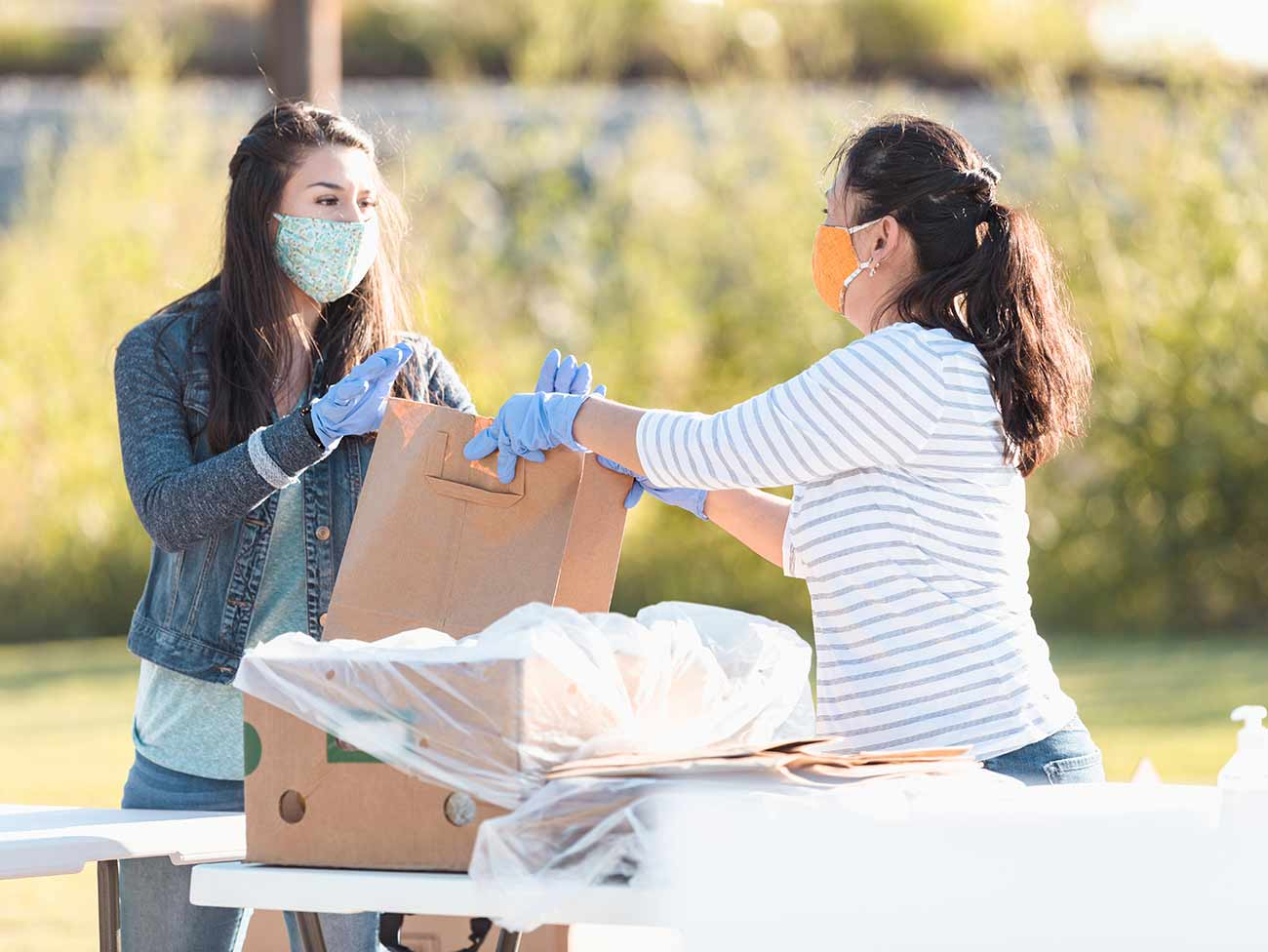 2 women in an outdoor setting wearing masks and latex gloves preparing supplies for distribution