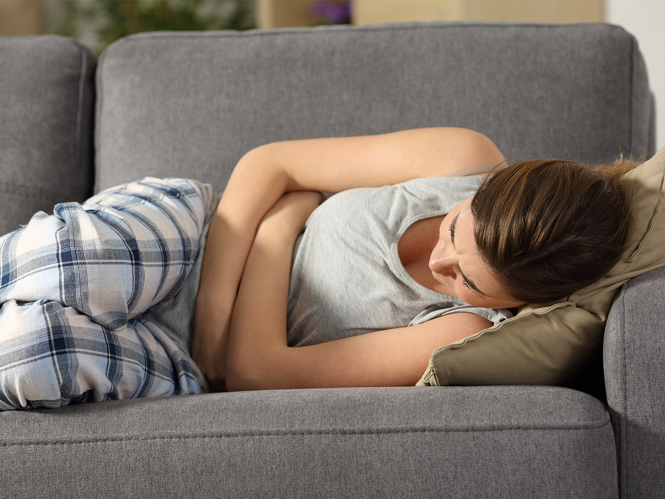 Woman laying on a couch holding her stomach