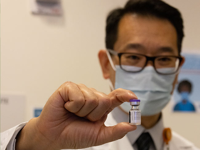 Pharmacy director, David Cheng, safely removes a vial of the first COVID-19 vaccine given in California.