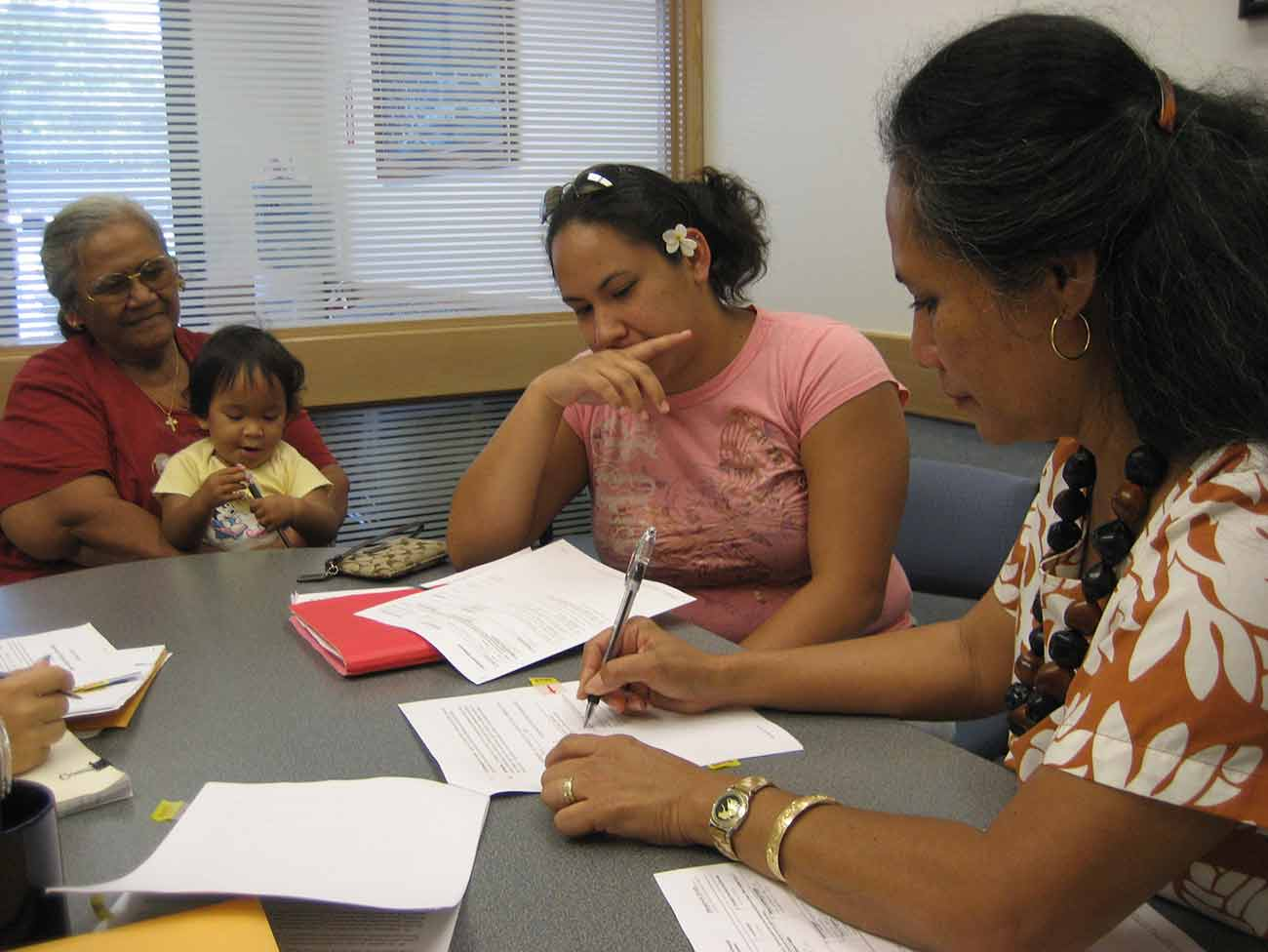 3 women seated at a table filling out paperwork