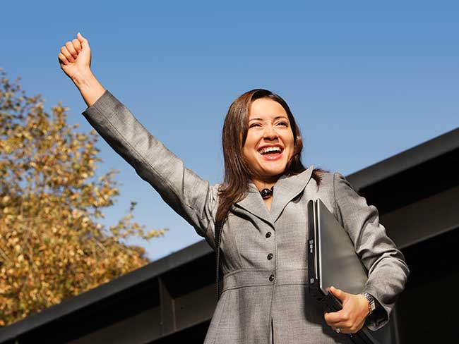 A young woman in a business suit with a fist raised over her head.