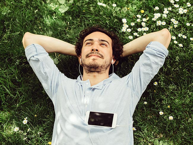 A smiling young man laying in the grass, hands behind his head, wearing earbuds with his mobile phone on his chest.
