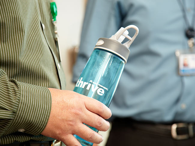 man's hand holding water bottle branded with Thrive