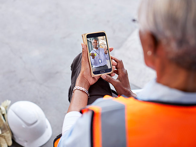 Looking over a female construction workers shoulder. She's on a mobile phone with her physician, during a telehealth visit.