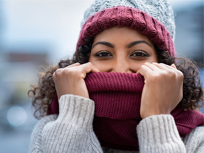 Happy African American woman posing with sweater and scarf