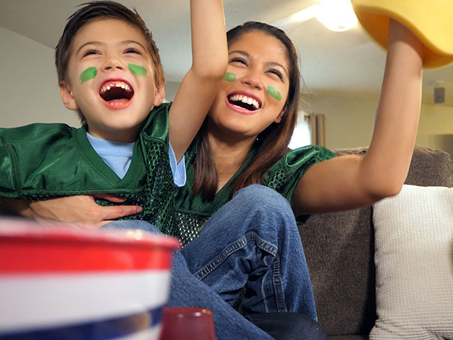 A happy mother and young child wearing sports jerseys while watching a game on the television.