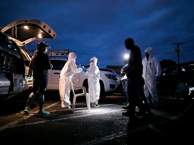 People dressed in PPE, assisting a patient in a lit parking lot, during evening hours.