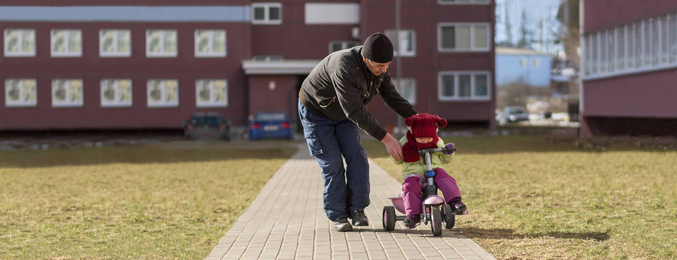 A man teaching his young child how to ride a tricycle out in front of a housing complex.