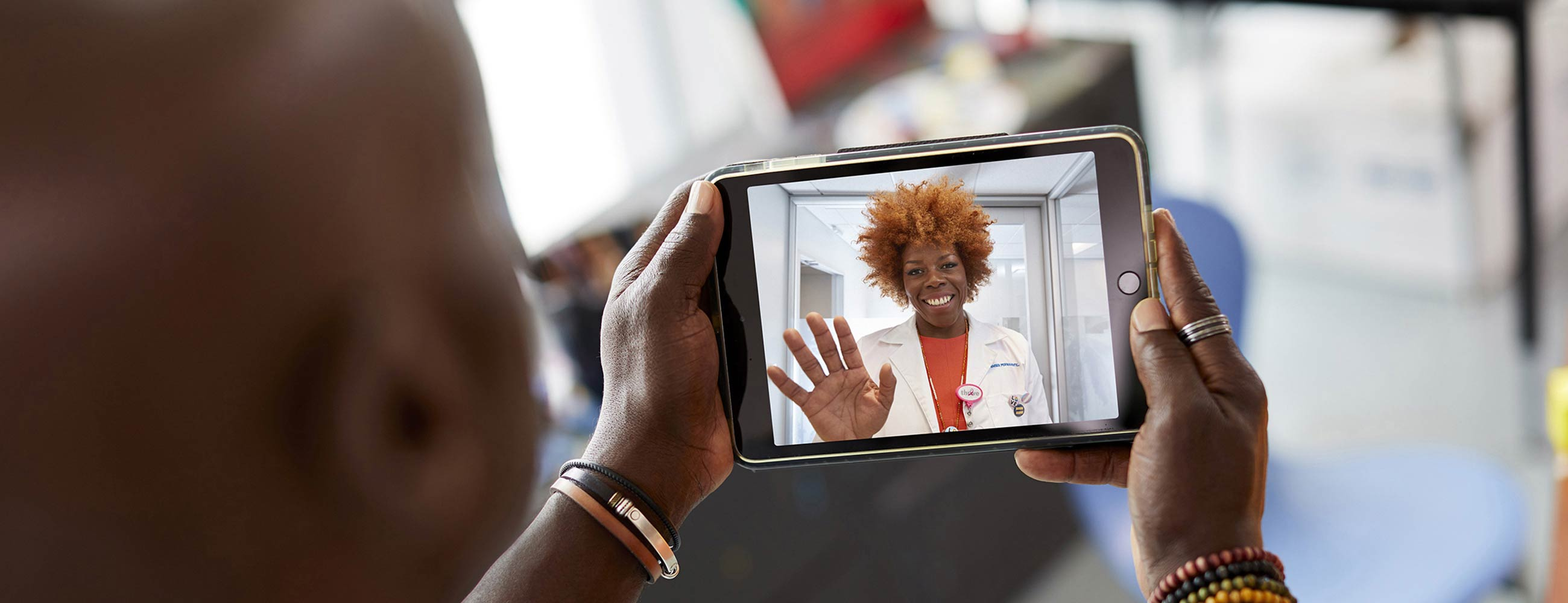 A smiling female physician waving while her patient holds a tablet during a telehealth visit.