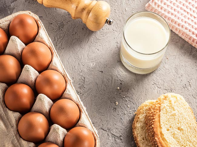 Aerial shot featuring carton of eggs, salt grinder, glass of milk, and bread