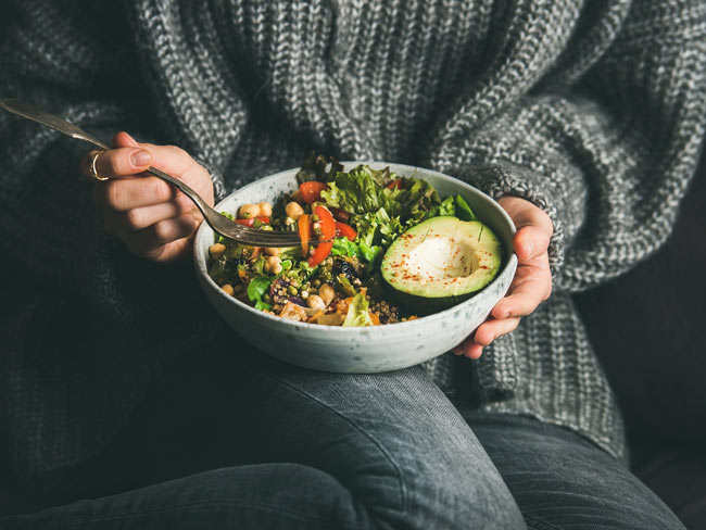 Person holding bowl of veggies on their lap