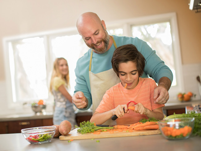 Father helping sun cut carrots at kitchen counter