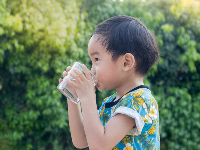 young boy in an outdoor setting drinking a glass of water