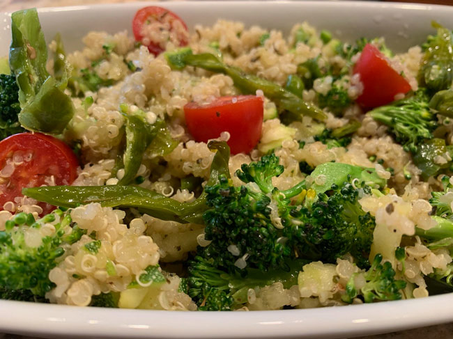 Broccoli, tomatoes, and Shishito peppers on top of quinoa in bowl