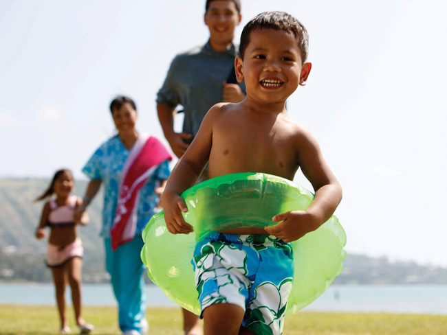 young boy at the beach wearing inflatable ring around his waist