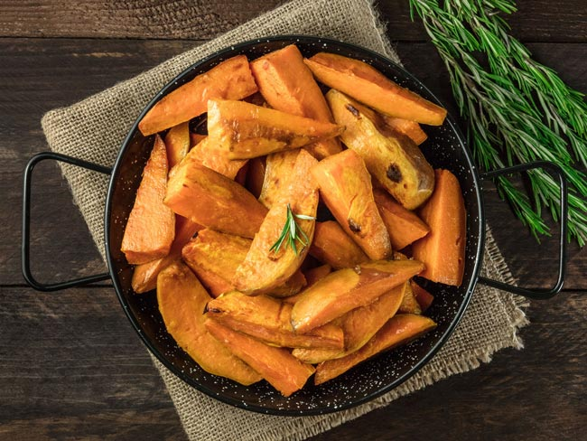 baked sweet potato wedges with a garnish of rosemary