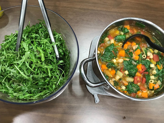 Greens in glass bowl on left and soup with spinach, butternut squash, carrots, and other vegetables in pot on right.