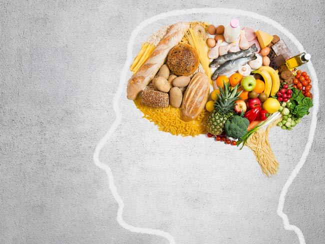Silhouette outline of human head, with various foods depicted in brain.