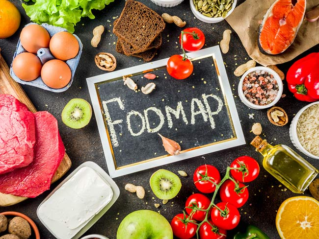 "Overhead photo of chalkboard with ""FODMAP"" written on it in center, surrounded by various foods, including tomatoes and eggs."