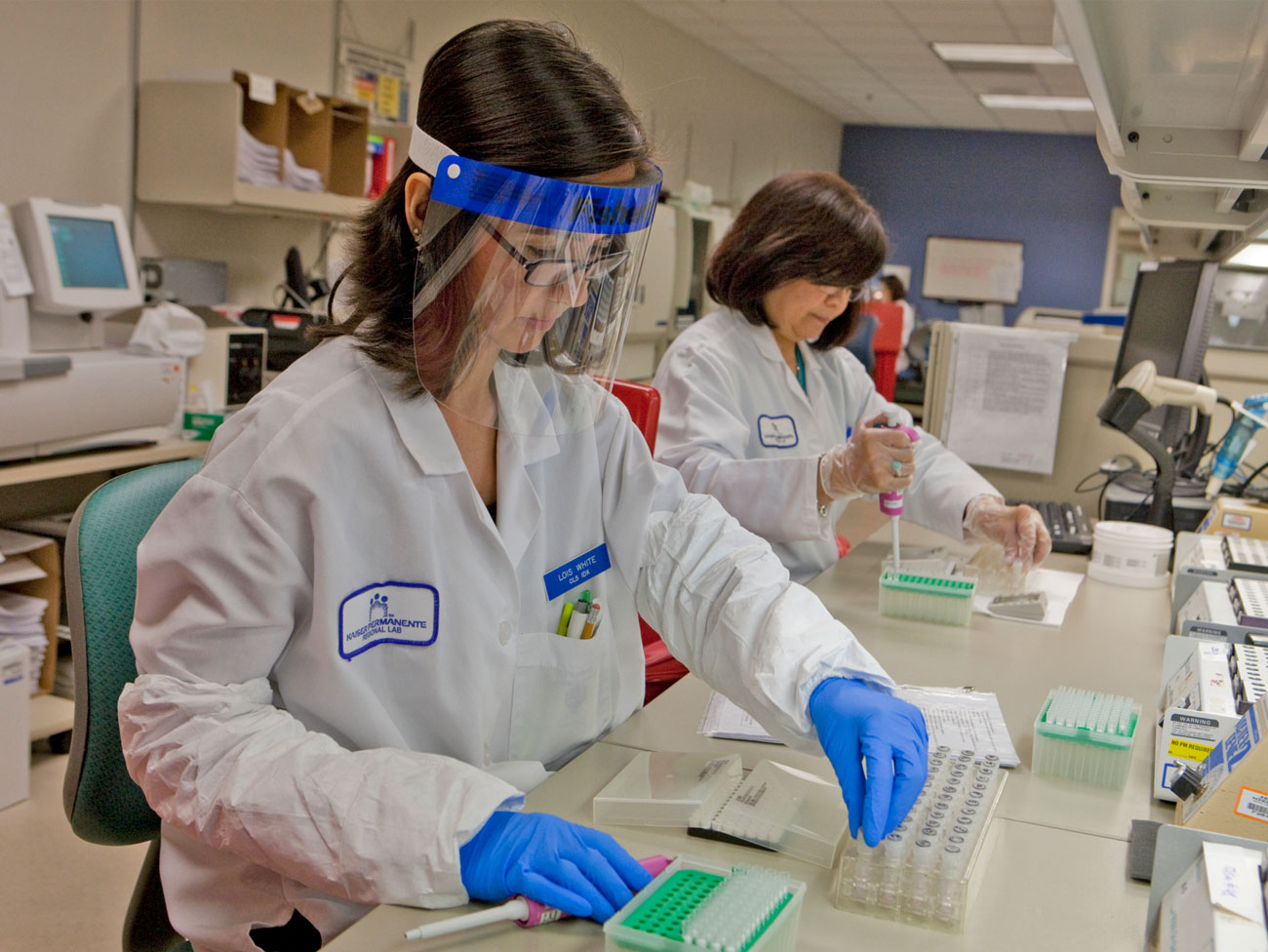 Two female laboratory professionals at work.