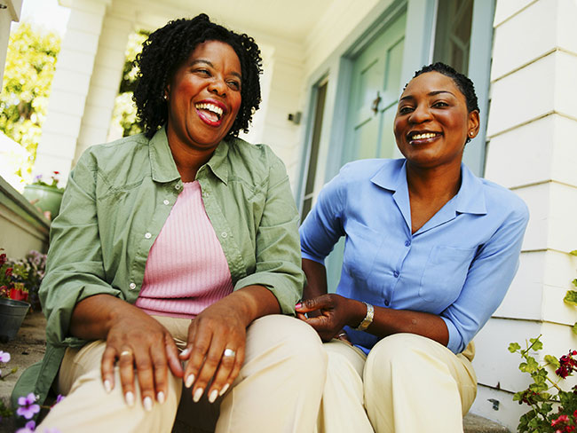 2 women sitting on porch and laughing