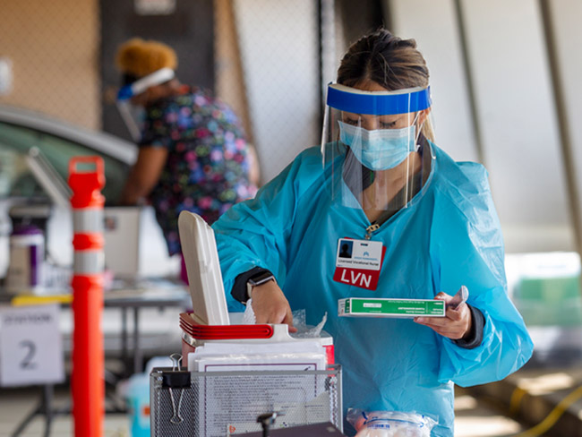 medical worker wearing protective gear and taking vaccine out of a container