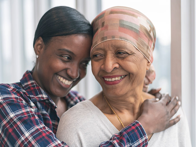 Black senior woman with cancer wearing a scarf on her head with her adult daughter giving her a hug and smiling