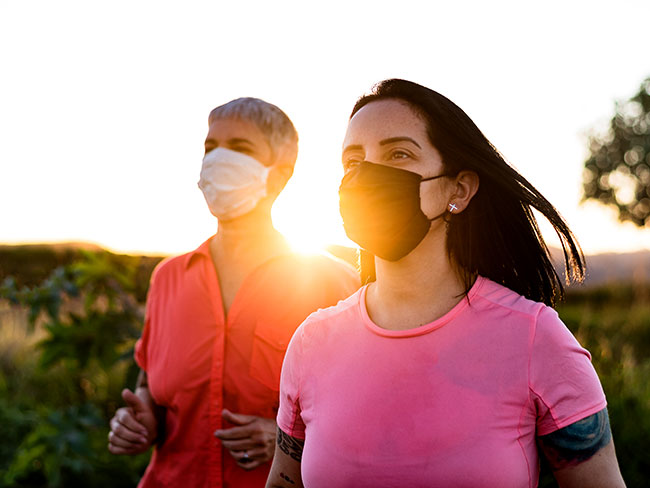 Women running at sunset, while wearing protective face masks.