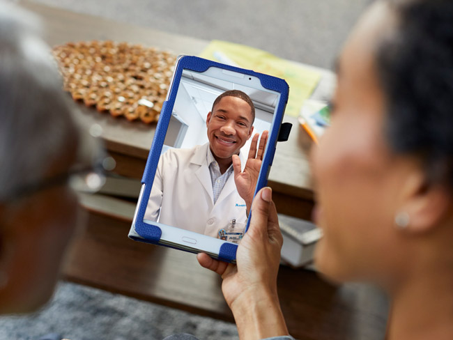 Physician smiling at members during a video visit on a tablet