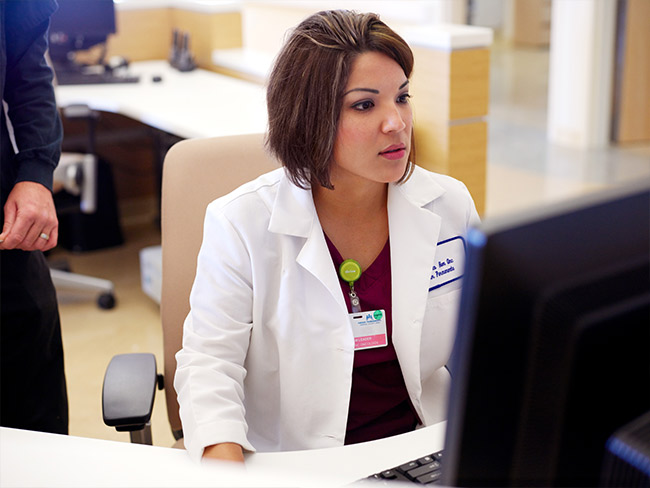 Health care worker sits at computer.