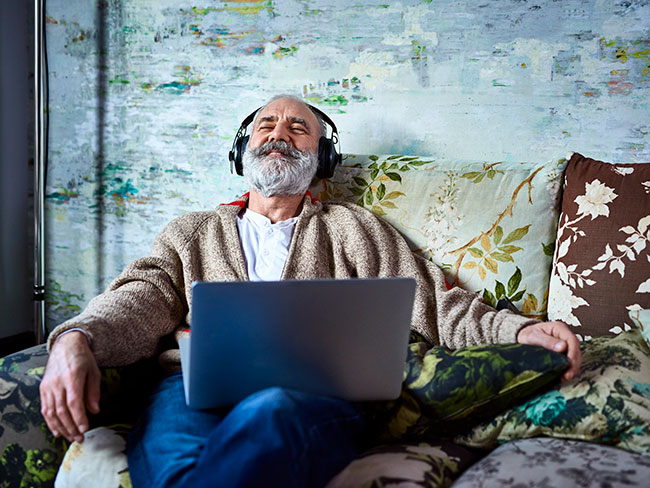 Smiling man relaxing at home, with laptop, wearing headphones, with eyes closed, listening to music.