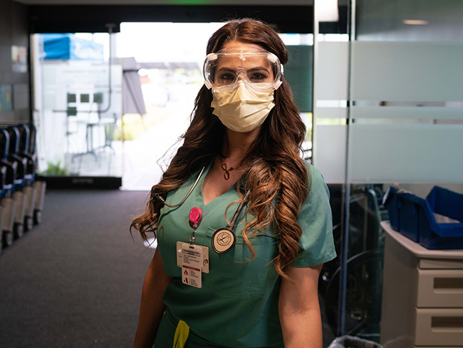 woman dressed in scrubs wearing goggles and protective mask