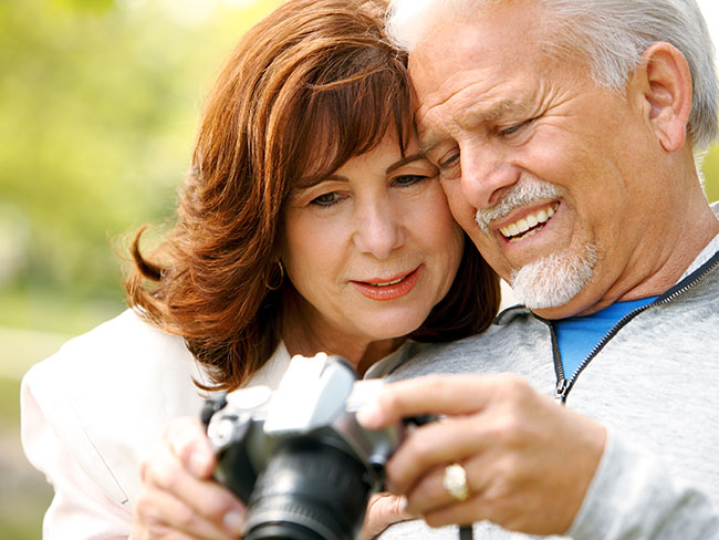 older woman and man looking at the screen of a digital camera and smiling