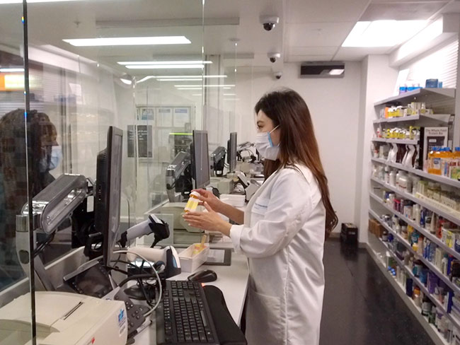 Pharmacist in face mask hands a member her prescription from behind plexiglass.