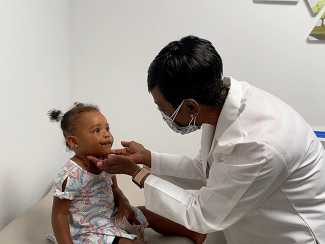 Female physician examining toddler girl