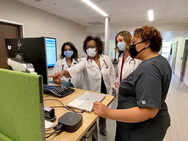 Health care workers reviewing a record on a computer
