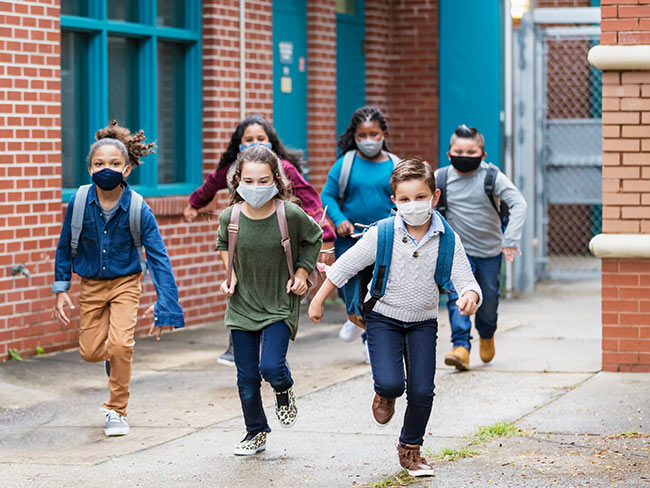 School-aged children wearing face masks outdoors