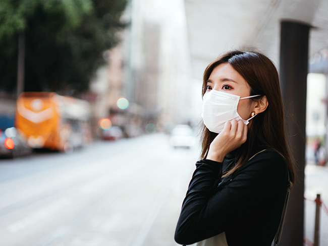 Young Asian woman wearing a protective face mask while waiting for public transportation.