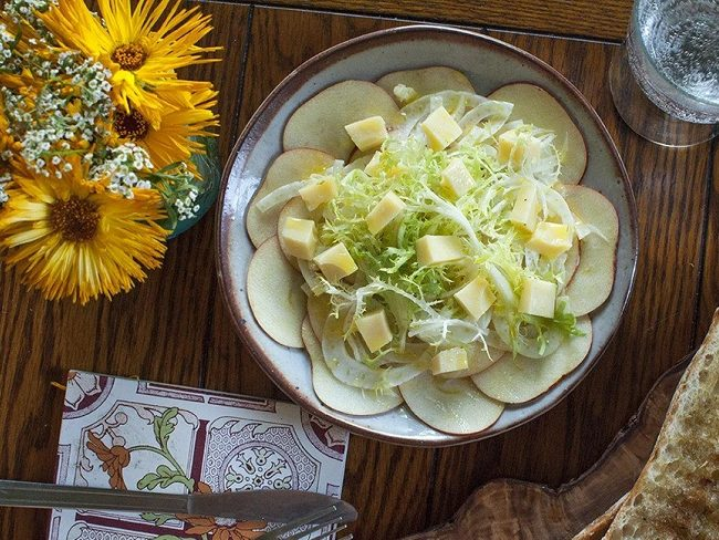 Shaved apple slices on plate, with fennel and Swiss cheese blocks on top